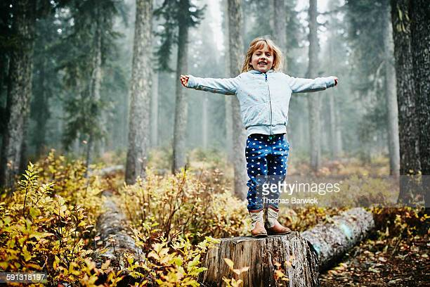 smiling young girl standing on log in woods - nur kinder stock-fotos und bilder
