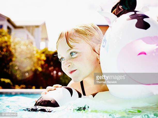 Smiling young girl swimming in backyard pool