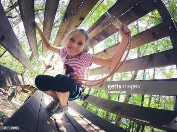 lächelnde junge mädchen zu fuß durch hängende tunnel im funpark - kinderspielplatz stock-fotos und bilder