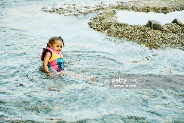 Smiling young girl wearing life jacket sitting in river on summer afternoon
