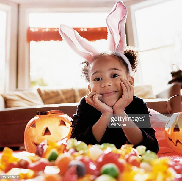 smiling young girl wearing rabbit ears lying on the floor with lots of candy - large group of objects stock pictures, royalty-free photos & images