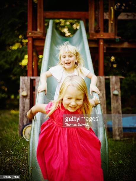 Smiling young girls riding down slide laughing