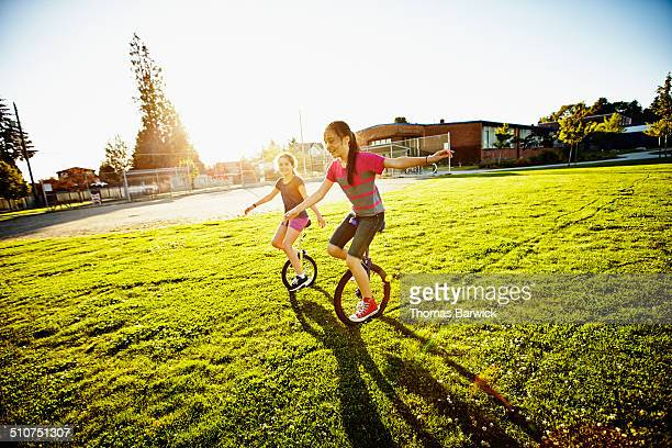 Smiling young girls riding unicycles on field