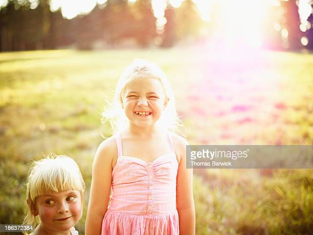 Smiling young girls standing in field at sunset