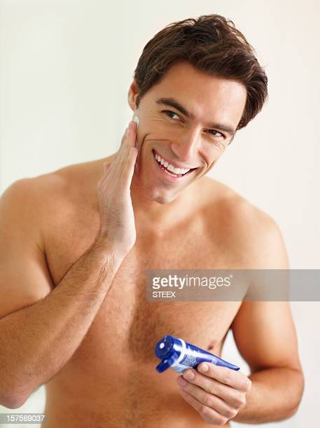 Smiling young guy applying shaving cream from the tube