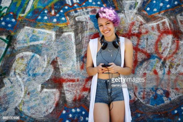 Smiling young hipster girl using smart phone against graffiti wall