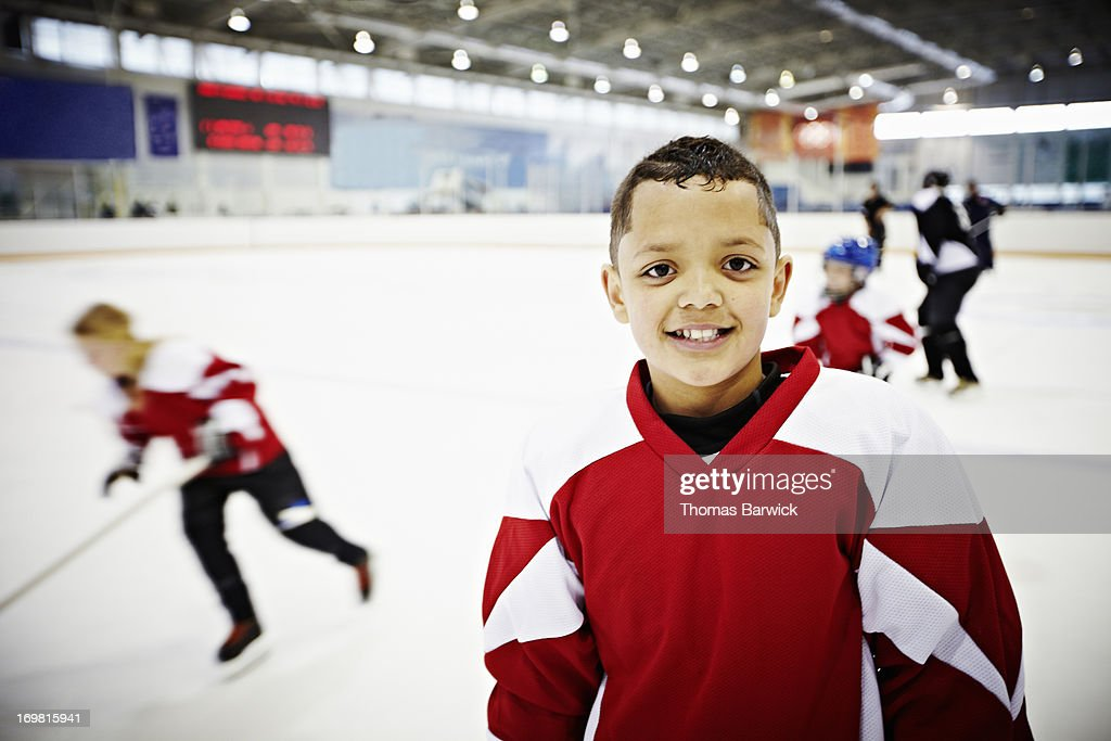 Smiling young hockey player standing on ice : Stock Photo