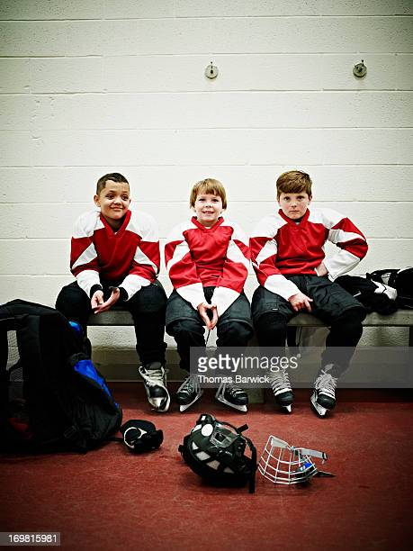 Smiling young hockey players in locker room