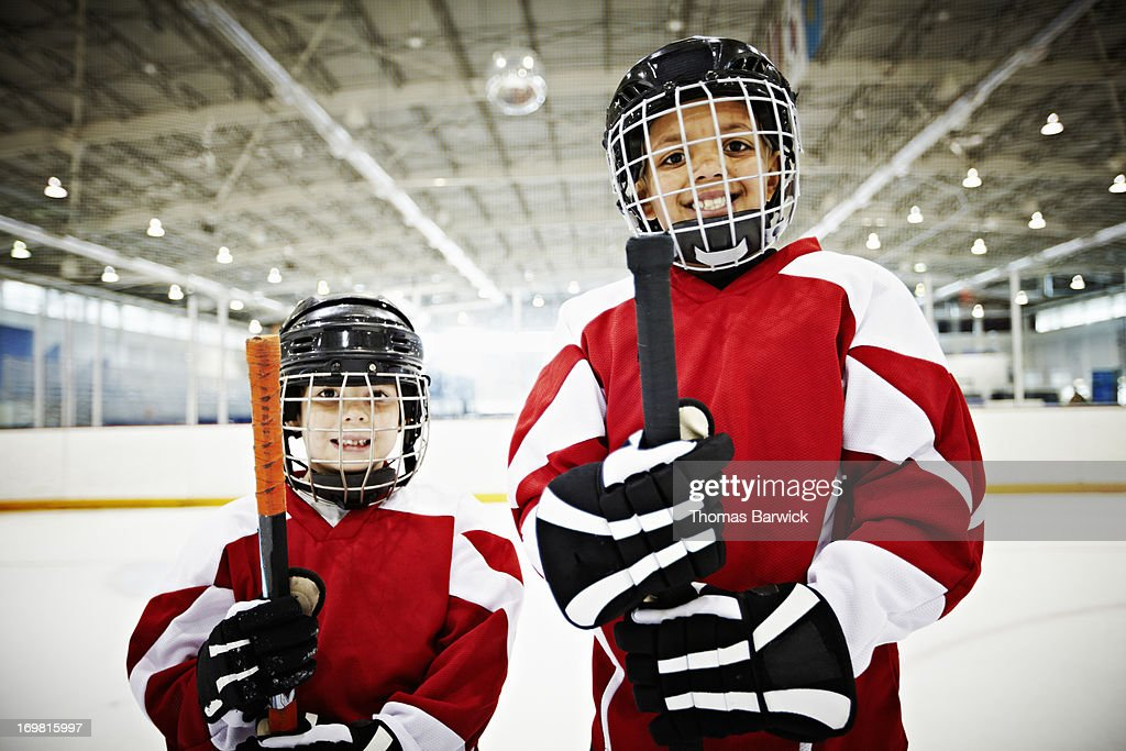 Smiling young hockey players standing on ice : Stock Photo