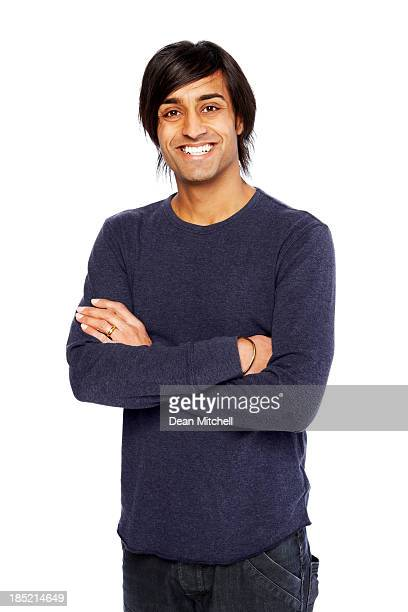 Smiling young Indian guy standing on white