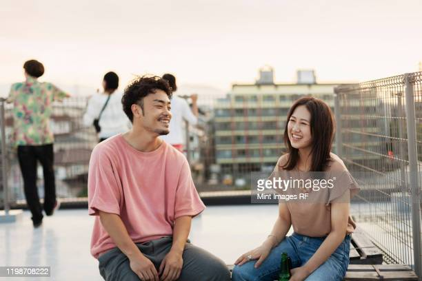 smiling young japanese man and woman sitting on a rooftop in an urban setting. - 女性 ストックフォトと画像