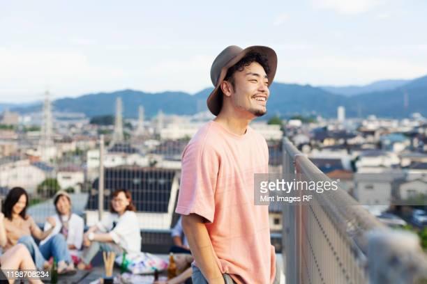 smiling young japanese man standing on a rooftop in an urban setting. - japanischer abstammung stock-fotos und bilder