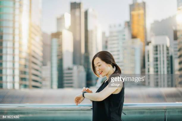 Smiling young lady checking smart watch in city, with skyline of busy financial district as background