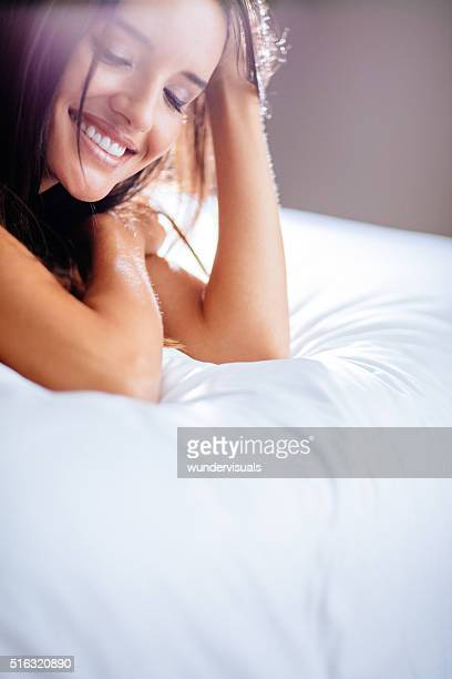 Smiling young lady in bed. Close-up of her face