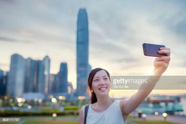 smiling young lady taking selfie on smartphone - ärmellos stock-fotos und bilder