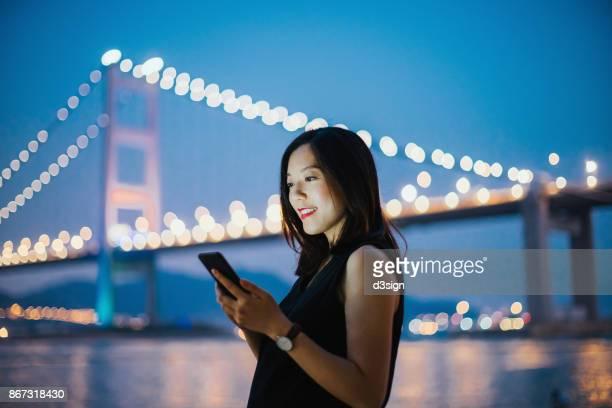 smiling young lady using cell phone against urban bridge at dusk - paisajes de china fotografías e imágenes de stock