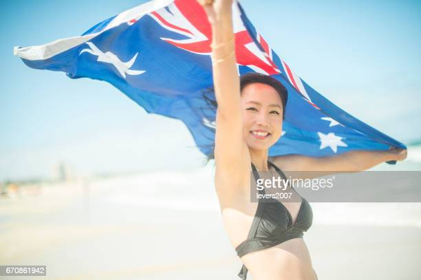 Smiling young lady with Australian flag on beach