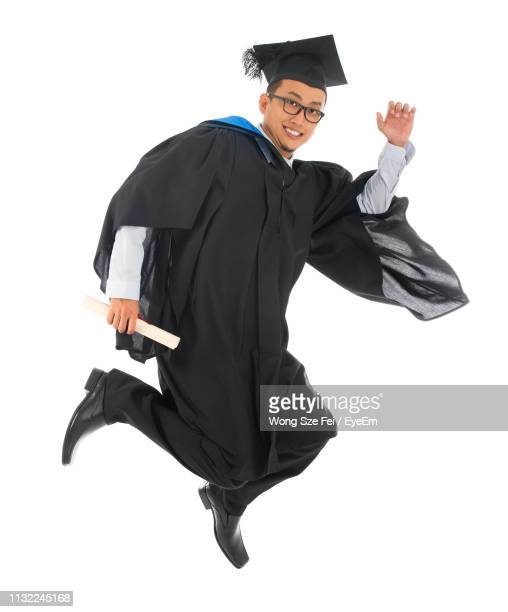 smiling young man against white background - graduation background stock pictures, royalty-free photos & images
