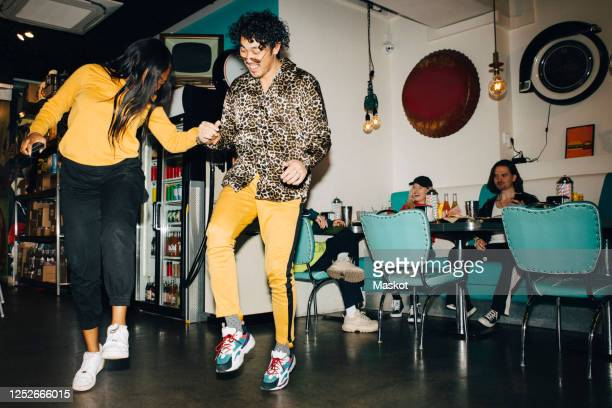 smiling young man and woman dancing while friends watching in background in cafe - mischief stock pictures, royalty-free photos & images