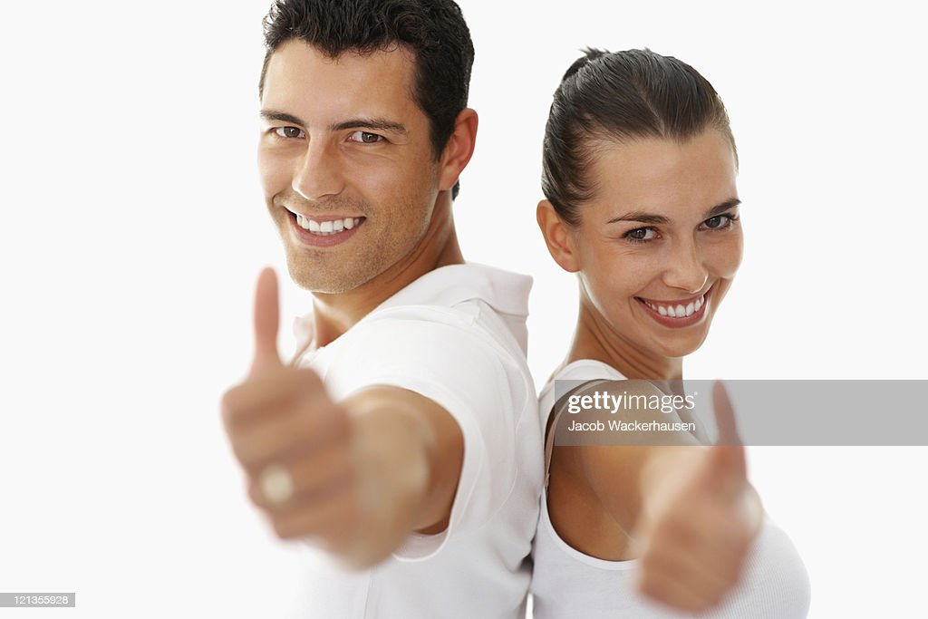 Smiling young man and woman giving a thumbs-up : Stock Photo