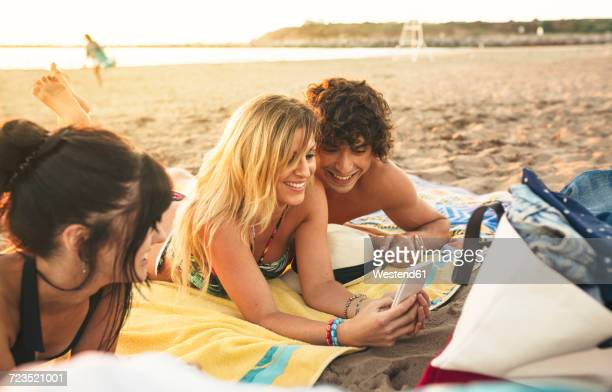 Smiling young man and woman sharing cell phone on the beach