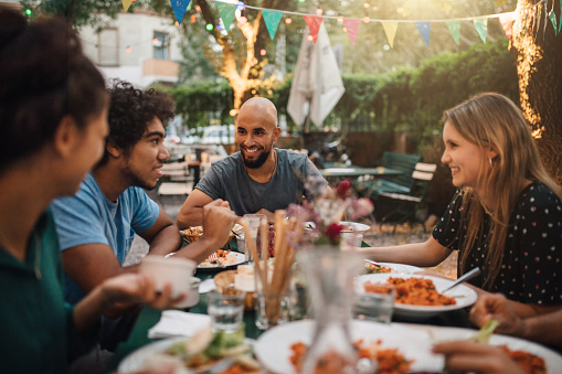 Smiling young man and women listening to male friend talking during dinner party in backyard - gettyimageskorea