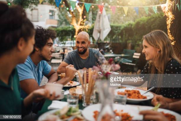 smiling young man and women listening to male friend talking during dinner party in backyard - warmes abendessen stock-fotos und bilder
