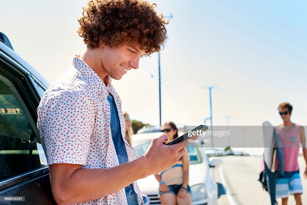 Smiling young man at a car checking his cell phone : Stock-Foto