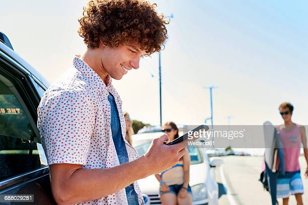 Smiling young man at a car checking his cell phone