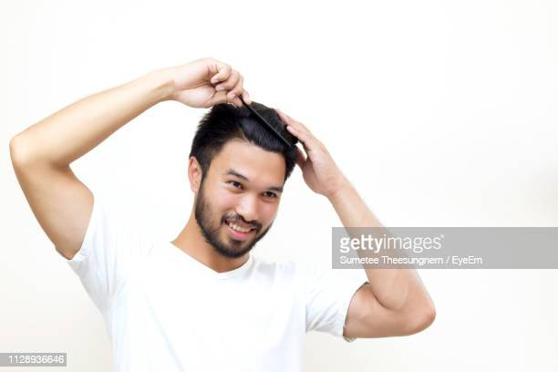 smiling young man combing against white background - penteando imagens e fotografias de stock