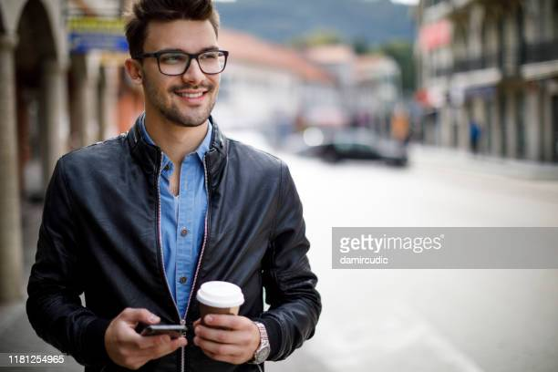 smiling young man commuting to work - damircudic stock photos and pictures