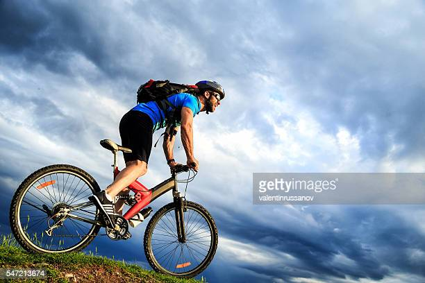 Smiling young man cycling on top