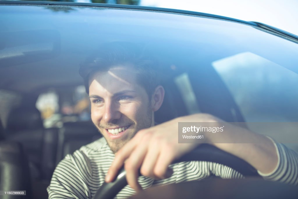 Smiling young man driving car : Stock-Foto
