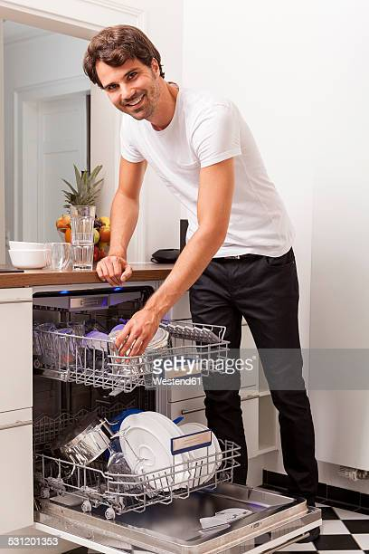 Smiling young man emptying the dishwasher