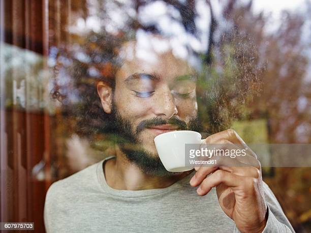 smiling young man enjoying cup of coffee behind windowpane - lebensfreude stock-fotos und bilder