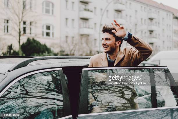 Smiling Young Man Entering Car