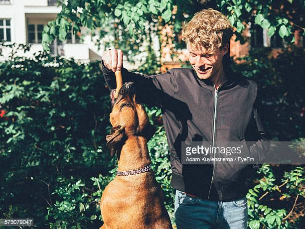Smiling Young Man Feeding Sausage To Dog In Yard