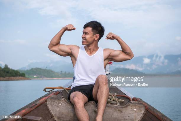 smiling young man flexing muscles while sitting on rowboat against sky - flexing muscles stock pictures, royalty-free photos & images