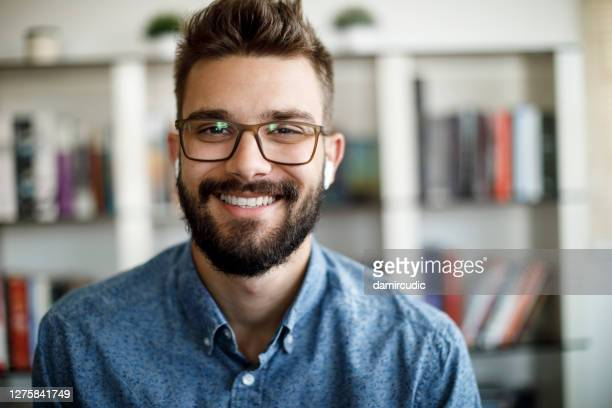 smiling young man having online conference from home - webcam stock pictures, royalty-free photos & images
