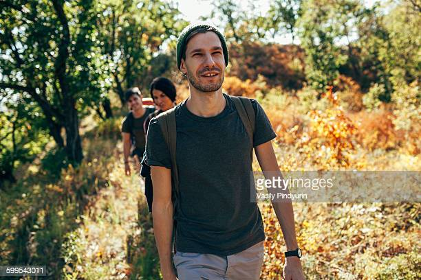 Smiling young man hiking with friends in forest