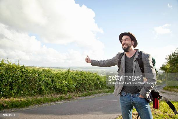 Smiling young man hitchhiking on rural road
