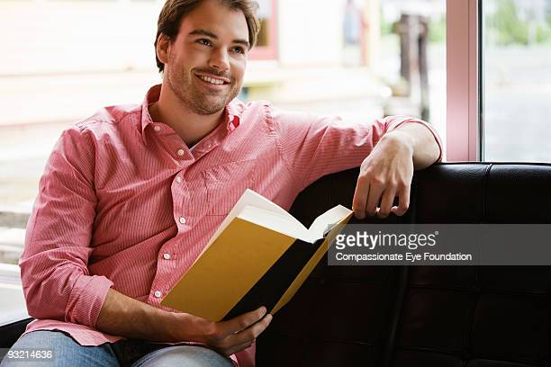 """smiling young man holding a book - """"compassionate eye"""" stock pictures, royalty-free photos & images"""