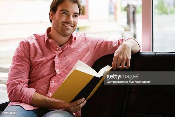 """smiling young man holding a book - """"compassionate eye"""" - fotografias e filmes do acervo"""