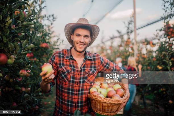 Smiling young man holding apples