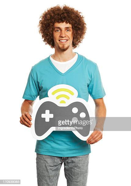 Smiling young man holding gamepad sign isolated on white background.