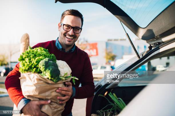 smiling young man holding grocery bag - groceries stock pictures, royalty-free photos & images