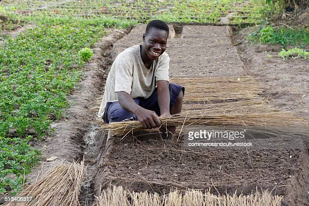 A smiling young man holding straw