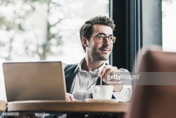 smiling young man in a cafe with laptop and cup of coffee - intelligenz stock-fotos und bilder