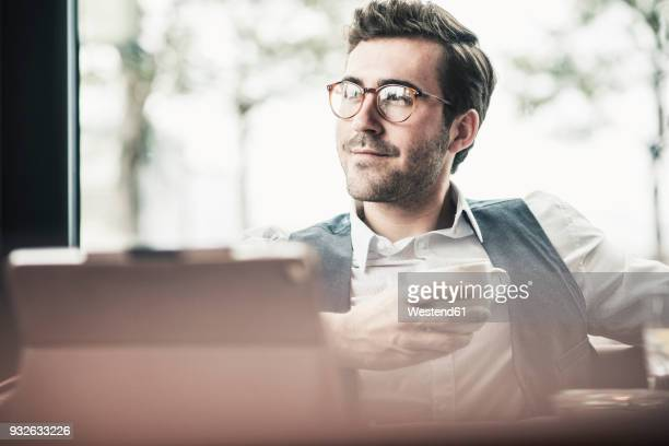 Smiling young man in a cafe with tablet and cup of coffee
