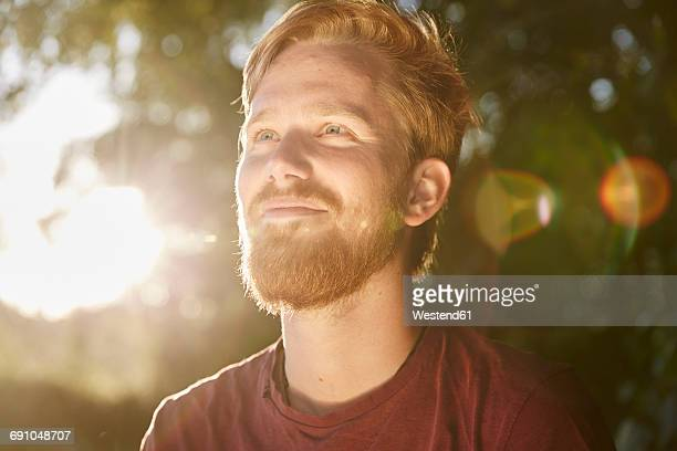 smiling young man in backlight outdoors - zonnestraal stockfoto's en -beelden
